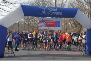 Runners gathered at the start of the race. You see them through a large arch colored blue and white