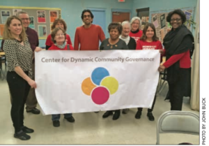 About 10 people in a room holding a banner that says Center for Dynamic Community Governance